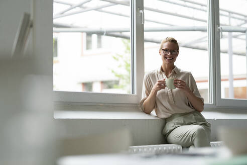 Portrait of smiling young businesswoman with cup of coffee sitting at the window - JOSF03530