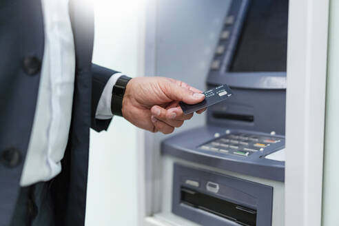 Mature businessman withdrawing money with credit card at an ATM - DIGF07415