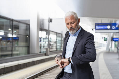 Mature businessman at the station platform checking the time - DIGF07451