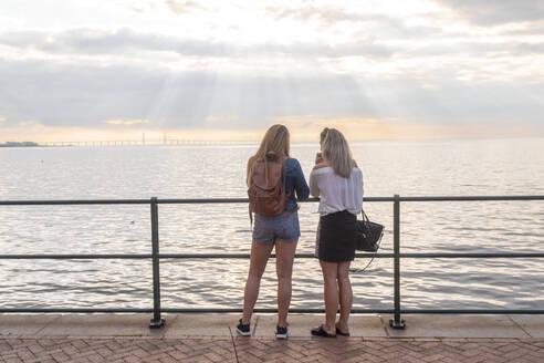 two femal friends taking photos by ostersund bridge in västrahamnen - TAMF01798