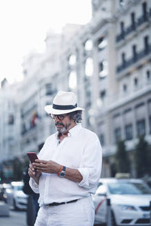 Senior man with white clothing and hat using smart phone in street of Madrid - OCMF00464