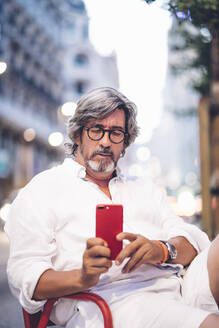 Senior man text messaging on mobile phone while sitting at sidewalk cafe in Madrid - OCMF00470