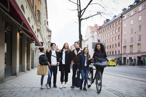Smiling male and female teenage friends walking on sidewalk in city - MASF12833
