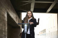 Portrait of smiling teenage girl with electric push scooter holding mobile phone below bridge - MASF12869