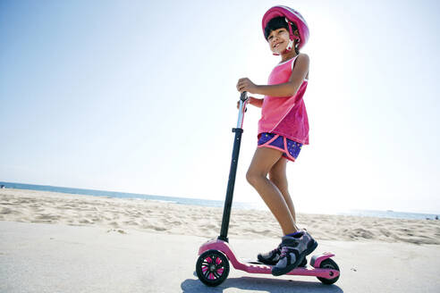Mixed race girl riding scooter at beach - BLEF09730