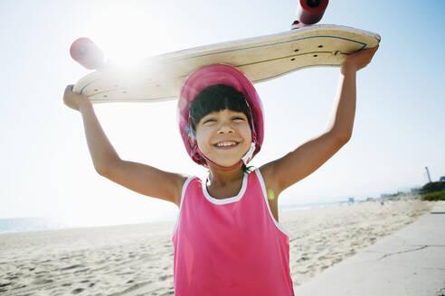 Mixed race girl holding skateboard at beach - BLEF09736