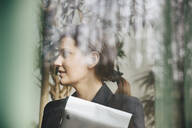 Confident businesswoman looking away seen through window at office - MASF12956