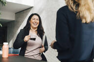 Smiling businesswoman having coffee while talking to colleague at conference - MASF12980