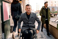 Disabled mature man looking away while sitting on wheelchair in city - MASF13007