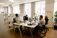 Business colleagues with disabled sales manager working at desk in office - MASF13055