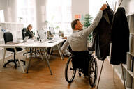 Rear view of disabled businessman hanging coat in office - MASF13058