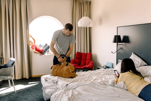 Man packing bag while woman using phone on bed in hotel - MASF13064