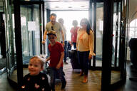 Smiling family entering hotel during vacations - MASF13088
