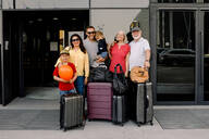 Portrait of happy family with luggage standing at hotel entrance - MASF13094