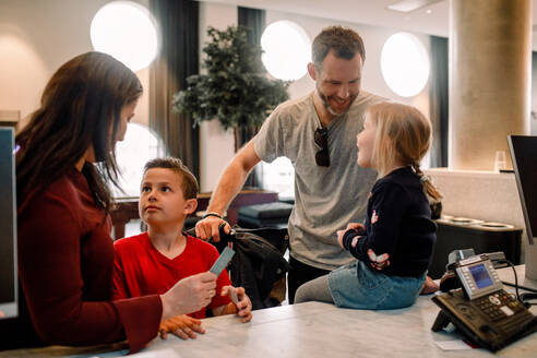 Smiling parents talking to children at reception in hotel - MASF13097
