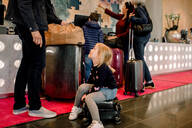 Girl sitting on suitcase while looking at father with family standing in background - MASF13103