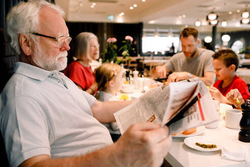Senior man reading newspaper while sitting family in restaurant during breakfast - MASF13106