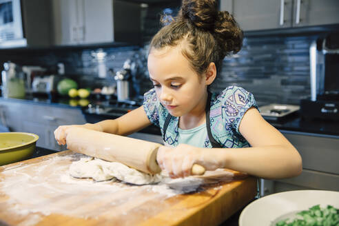 Mixed race girl rolling dough in kitchen - BLEF09832