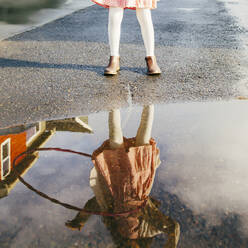 Mixed race girl and plastic hoop reflected in puddle - BLEF09835
