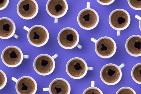 Directly above view of fresh coffee in cups over purple background - DRBF00158