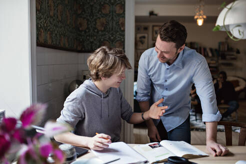 Smiling son thanking father for his help in doing homework at home - MASF13118