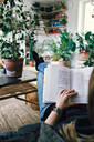 Mid adult woman reading book while relaxing at home - MASF13217