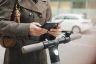 Midsection of female commuter using smart phone standing with electric vehicle in city - MASF13262