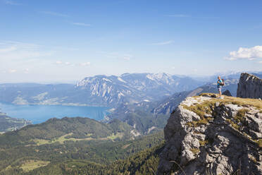 Full length of hiker standing on Spinnerin peak while looking at Attersee against blue sky - GWF06155