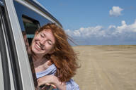 Carefree redhead teenage girl with head out of car window at beach against sky - LBF02623