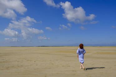 Full length rear view of teenage girl walking on sand at beach during sunny day - LBF02626