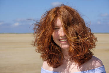 Close-up portrait of carefree redhead teenage girl standing at beach against sky on sunny day - LBF02632