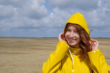 Close-up portrait of carefree redhead teenage girl wearing yellow raincoat while standing at beach against sky on sunny day - LBF02635