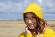 Close-up portrait of carefree redhead teenage girl wearing yellow raincoat at beach against sky on sunny day - LBF02638