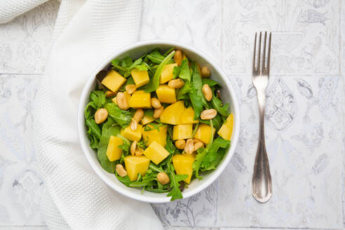 Close-up of fresh salad in bowl by napkin and fork on tiled floor - LVF08175