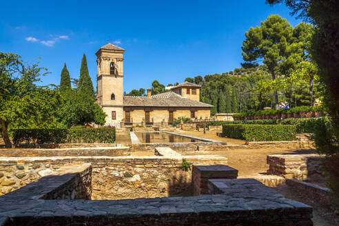 Historic Alhambra palace amidst trees against blue sky on sunny day - PU01685