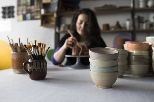 Potter shaping clay in her workshop, focus on foreground - ABZF02419