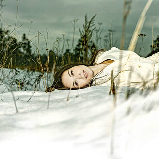 Caucasian woman laying in snow - BLEF09866