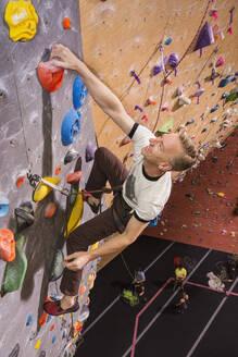 Caucasian man climbing rock wall - BLEF09944