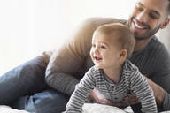Smiling father playing with baby son on bed - BLEF10054
