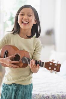 Chinese girl practicing ukulele in bedroom - BLEF10069