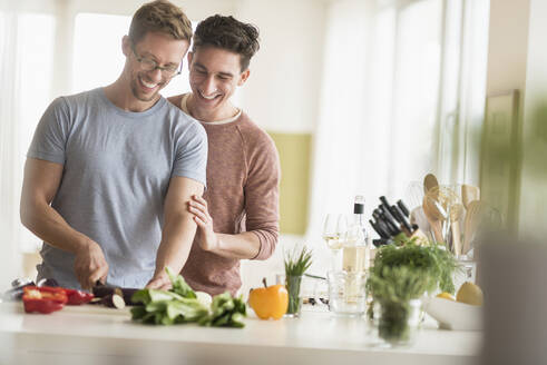 Caucasian gay couple cooking in kitchen - BLEF10078