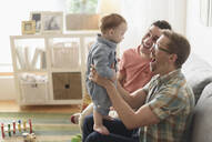 Caucasian gay fathers and baby playing in living room - BLEF10093