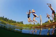 Kids jumping into sunny summer lake - FSIF04158