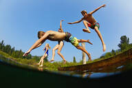 Playful kids jumping off dock into sunny summer lake - FSIF04161