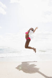 African American woman jumping for joy on beach - BLEF10180