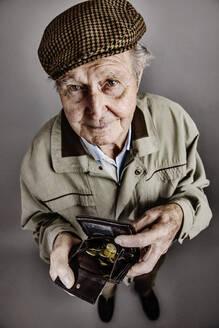 Portrait of senior man showing his purse - JATF01172