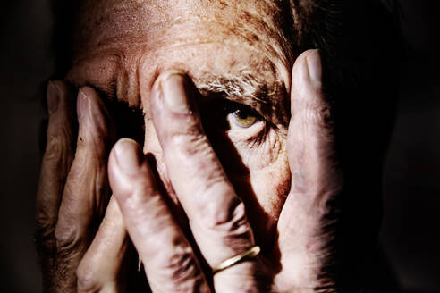 Senior man covering face with hands, close-up - JATF01175