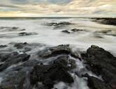 Volcanic rocks amidst water at Puuhonua O Honaunau National Historical Park against cloudy sky during sunset - CVF01283