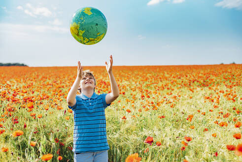 Happy boy catching globe while standing in poppy field against sky on sunny day - MJF02385