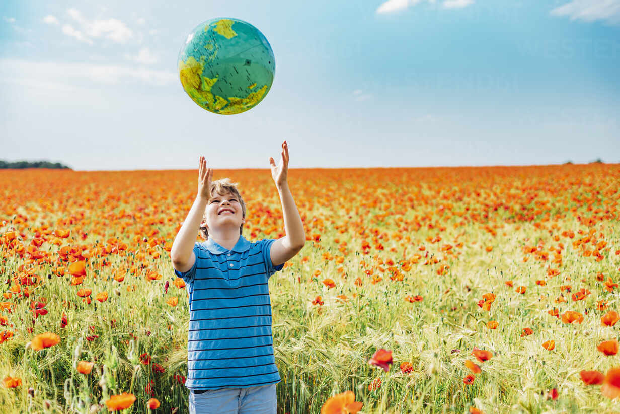 Happy boy catching globe while standing in poppy field against sky on sunny day - MJF02385 - Jana Mänz/Westend61
